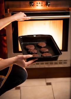 Zbliżenie zdjęcie gospodyni domowej, która stawia patelnię z ciastkami w piekarniku