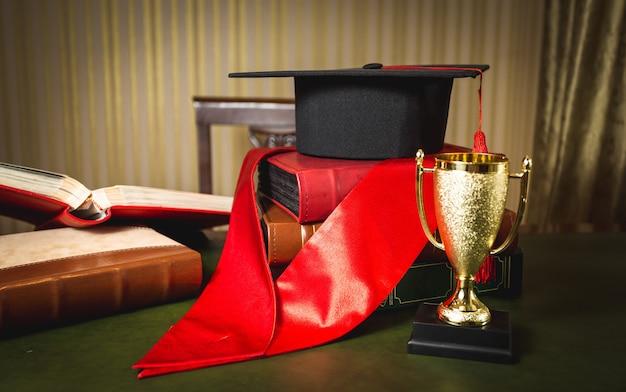 Zbliżenie zdjęcie kapelusza dyplomowego, czerwonej wstążki i złotego kubka za pierwsze miejsce