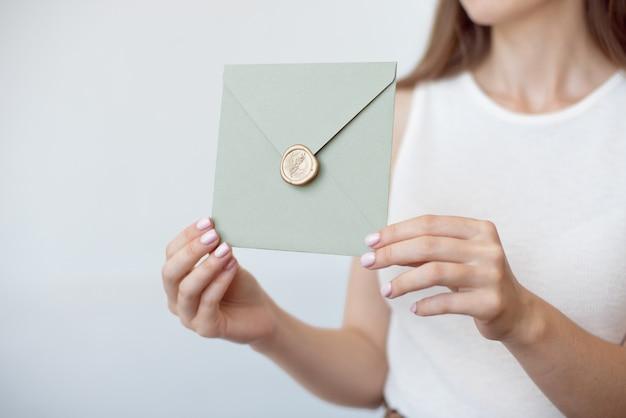 Zbliżenie zdjęcie kobiece ręce trzyma kopertę z woskową pieczęcią, bon upominkowy, pocztówka, karta zaproszenie na ślub.