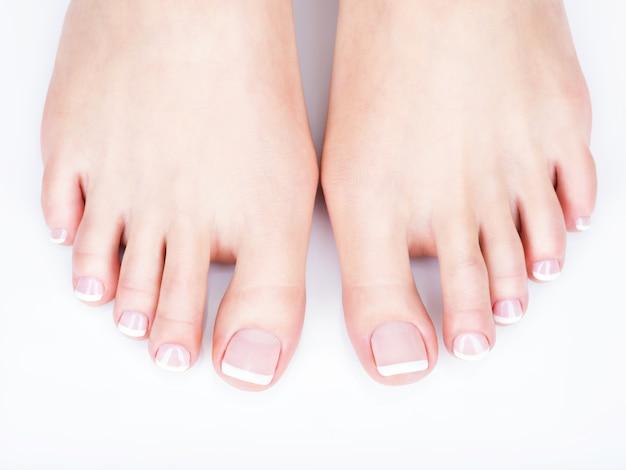Zbliżenie zdjęcie kobiecych stóp z białym pedicure francuskim na paznokciach