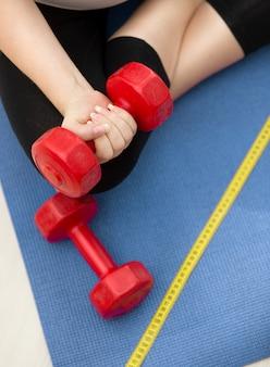 Zbliżenie zdjęcie kobiety ćwiczenia na macie fitness i podnoszenia czerwonych hantli