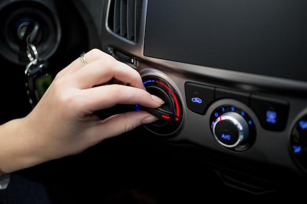 Zbliżenie zdjęcie kobiety dostosowującej temperaturę klimatyzatora samochodowego