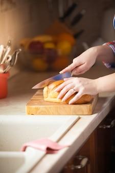 Zbliżenie zdjęcie kobiety krojącej chleb na drewnianym biurku