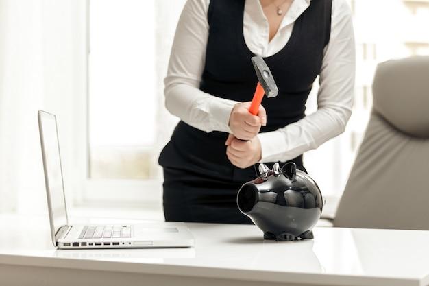 Zbliżenie zdjęcie kobiety łamiącej skarbonkę w biurze młotkiem