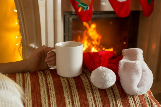 Zbliżenie zdjęcie kobiety siedzącej z filiżanką herbaty na kanapie przy kominku