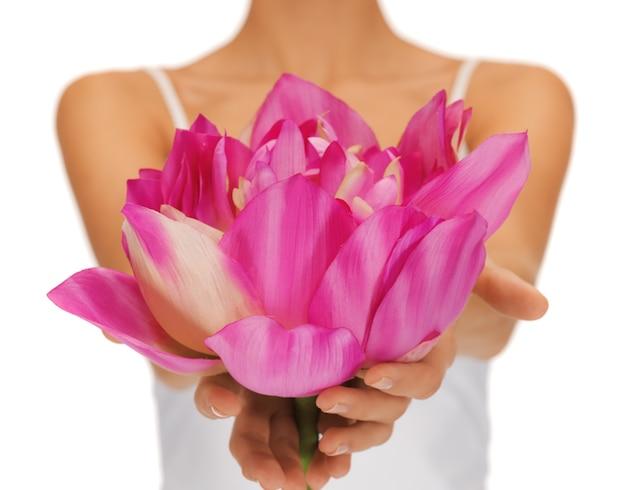 Zbliżenie zdjęcie kobiety trzymając się za ręce kwiat lotosu.
