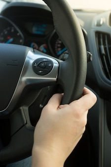 Zbliżenie zdjęcie kobiety trzymającej skórzaną kierownicę