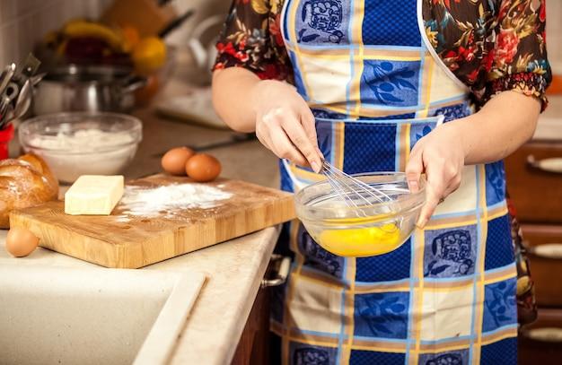 Zbliżenie zdjęcie kobiety ubijającej jajka w szklanej misce
