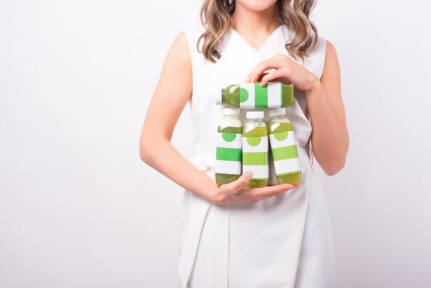 Zbliżenie zdjęcie kobiety w białej sukni, trzymającej wiele świeżych soków w butelce