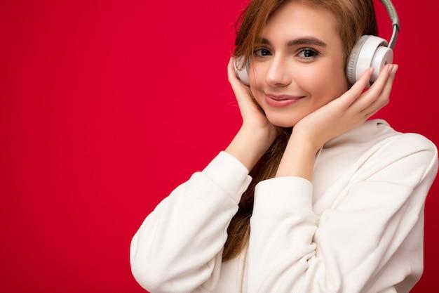 Zbliżenie zdjęcie ładny atrakcyjny pozytywny uśmiechający się młoda blondynka na sobie białą bluzę z kapturem na białym tle
