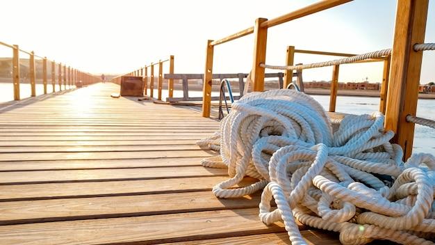 Zbliżenie zdjęcie lin leżących na drewnianym pokładzie długiego molo na wybrzeżu morza