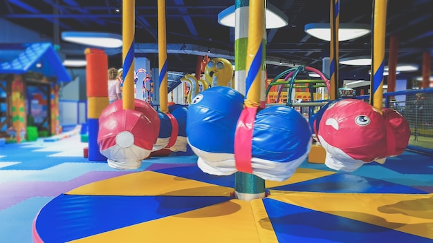 Zbliżenie zdjęcie małej kolorowej karuzeli dla małych dzieci pokryte matami saoft dla bezpieczeństwa dzieci na placu zabaw w parku rozrywki