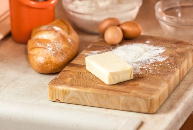 Zbliżenie zdjęcie masła, jajek i mąki leżące na drewnianej desce