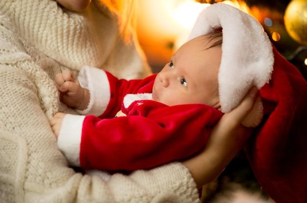 Zbliżenie zdjęcie matki trzymającej chłopca w stroju świętego mikołaja i kapeluszu