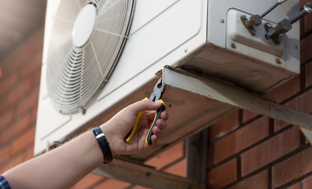 Zbliżenie zdjęcie męskiego technika instalującego klimatyzator zewnętrzny