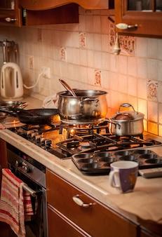 Zbliżenie zdjęcie metalowej patelni gotującej się na płonącej kuchence gazowej w kuchni w stylu wiejskim