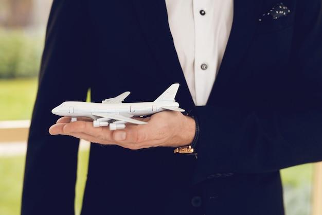Zbliżenie zdjęcie mężczyzny w czarnym garniturze trzymać samolot.