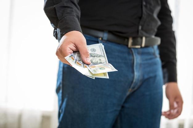 Zbliżenie zdjęcie mężczyzny w dżinsach i koszuli, trzymając banknoty sto dolarów