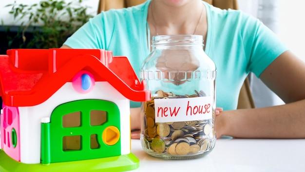 Zbliżenie zdjęcie młodej damy w niebieskiej koszulce siedzącej przy białym stole, na którym znajduje się mały dom i pełen monet, słoik z napisem nowy dom