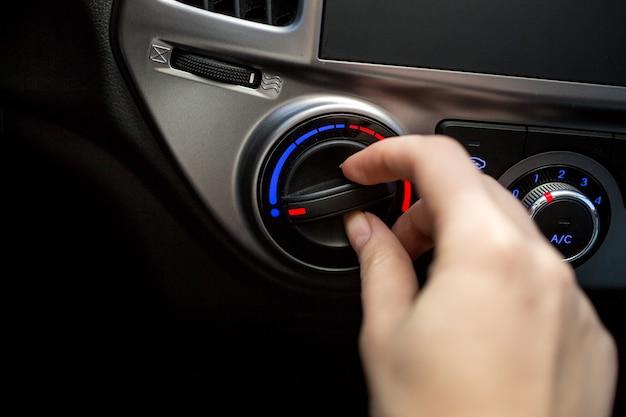 Zbliżenie zdjęcie młodej kobiety obracającej przełącznik klimatyzacji samochodowej