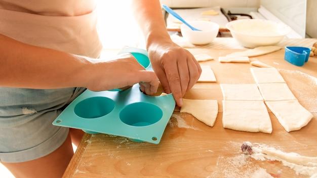 Zbliżenie zdjęcie młodej kobiety robi babeczki w domu. gospodyni układająca kawałki ciasta w silikonową formę
