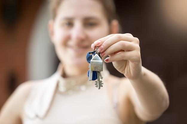 Zbliżenie zdjęcie młodej kobiety trzymającej klucz z nowego domu