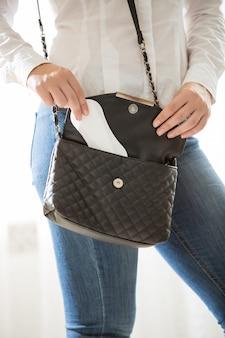 Zbliżenie zdjęcie młodej stylowej kobiety stawiając podkładkę higieniczną w torebce
