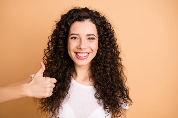 Zbliżenie zdjęcie niesamowitej pani biznesu podnosząc kciuk do góry ząb promienieje uśmiechnięty doradzając nowość nosić biały strój na co dzień na białym tle beżowy pastelowy kolor tła
