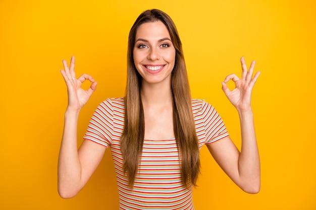 Zbliżenie zdjęcie niesamowitej pani pokazującej okey symbole toothy promienieje uśmiechnięty wyrazić pozytywne nastawienie nosić casualową koszulkę w paski na białym tle żółty kolor ściany