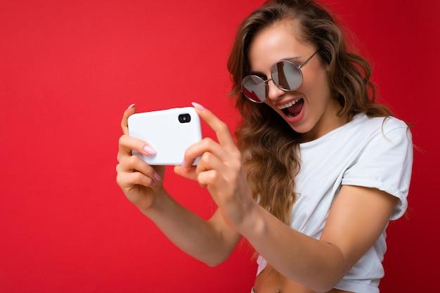 Zbliżenie zdjęcie niesamowitej pięknej młodej blondynki osoby posiadającej telefon komórkowy przy selfie