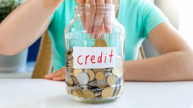 Zbliżenie zdjęcie pani w koszulce siedzącej przy białym stole, na którym znajduje się, pełen monet, słoik z napisem kredyt