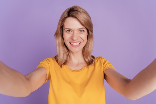 Zbliżenie zdjęcie piękna kobieta szczęśliwy pozytywny uśmiech sprawia, że robisz selfie izolowane nad fioletowym kolorem tła