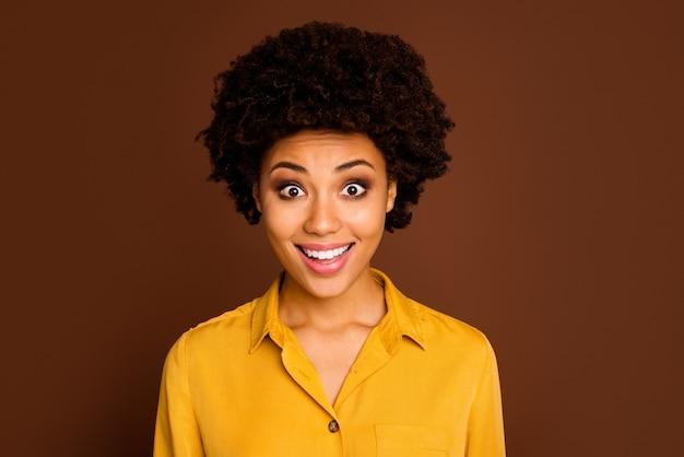 Zbliżenie zdjęcie pięknej całkiem ciemnej skóry kręcone pani otwarte usta wesoły wyraz twarzy słuchać niesamowite dobre wieści nosić żółtą koszulę na białym tle brązowy kolor