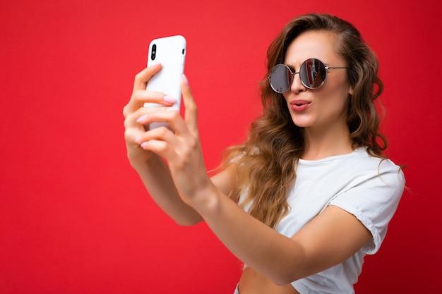 Zbliżenie zdjęcie pięknej młodej kobiety blondynka trzyma telefon komórkowy biorąc selfie zdjęcie za pomocą