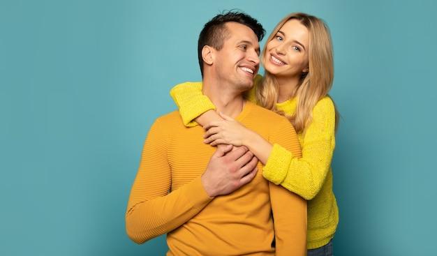 Zbliżenie zdjęcie pięknej zakochanej pary, która przytula się i uśmiecha, patrząc w kamerę.