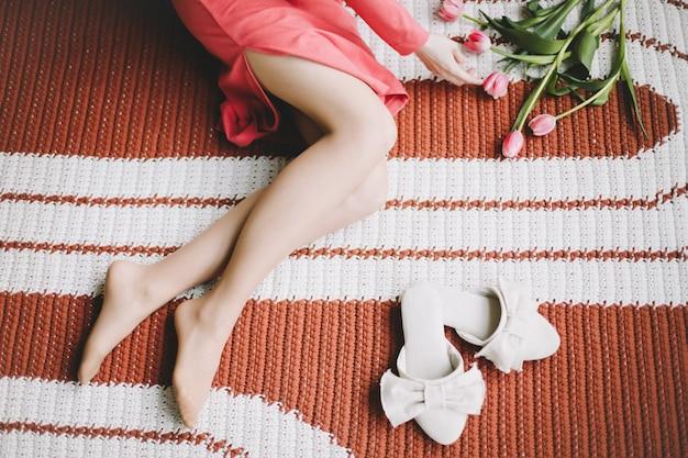 Zbliżenie zdjęcie pięknych nóg kobiety opalone nogi kobiety w pobliżu kwiatów i kapci