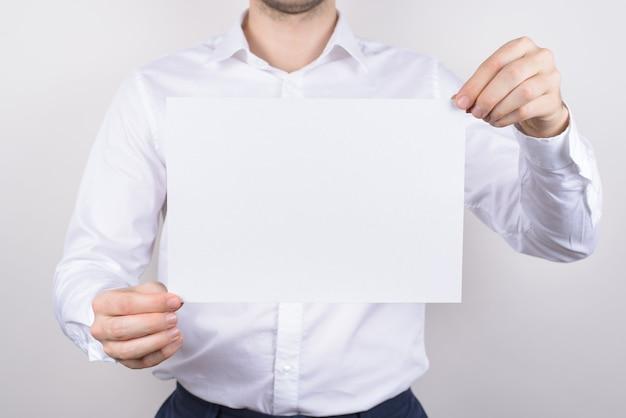 Zbliżenie zdjęcie portret przystojny poważny facet trzymając biały jasny czysty papier w ręce na białym tle szarym tle copyspace