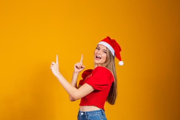 Zbliżenie zdjęcie pozytywne dziewczyny w kapeluszu świętego mikołaja wskazując palcem wskazującym, copyspace bezpośredni sposób x-mas boże narodzenie nowy rok reklamy promocja na białym tle żółty kolor tła
