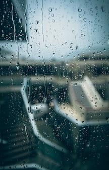 Zbliżenie zdjęcie przez okno z kroplami w deszczowy dzień