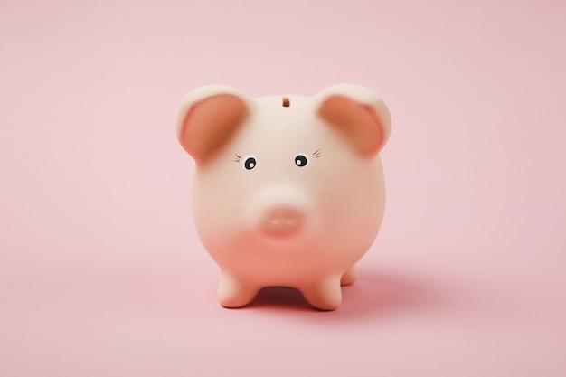 Zbliżenie zdjęcie różowej skarbonki na białym tle na tle ściany pastelowe różowe. akumulacja pieniędzy, inwestycje, usługi bankowe lub biznesowe, koncepcja bogactwa. skopiuj makiety reklamowe.