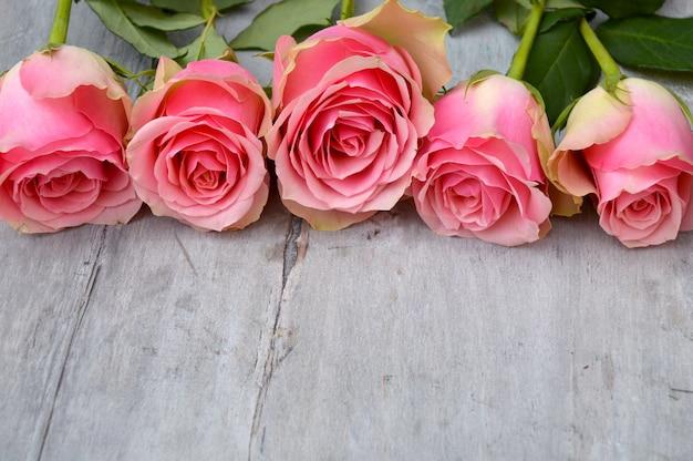 Zbliżenie zdjęcie różowych róż aksamitnych na powierzchni drewnianych