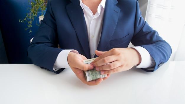 Zbliżenie zdjęcie skorumpowanego urzędnika trzymającego w ręku łapówkę pieniężną