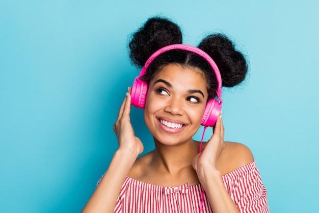 Zbliżenie zdjęcie śmiesznej ładnej ciemnej skóry pani słuchać muzyki nowoczesne technologie słuchawki wyglądają marzycielskiej pustej przestrzeni nosić modną czerwoną białą koszulę w paski poza ramionami na białym tle niebieski kolor ściany