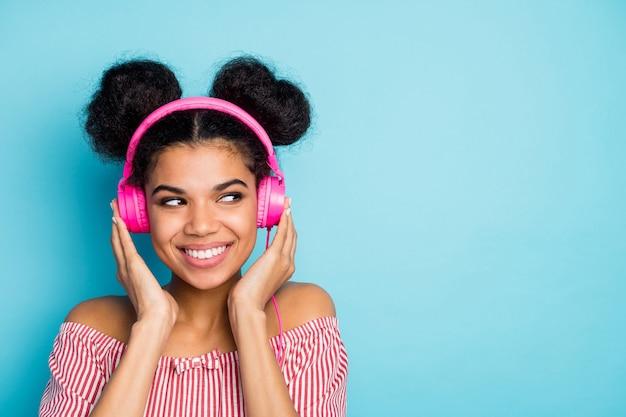 Zbliżenie zdjęcie śmiesznej zainteresowanej ciemnej skóry pani słuchać muzyki nowoczesne słuchawki wyglądają po stronie pustej przestrzeni nosić modną czerwoną białą koszulę w paski poza ramionami na białym tle niebieski kolor ściany