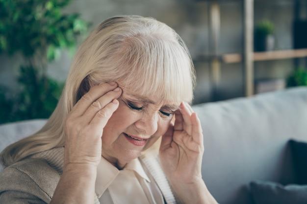 Zbliżenie zdjęcie starszej babci pani trzymając się za ręce na skroniach cierpiących straszny wiek migrena senny siedzący komfort sofa kanapa salon w pomieszczeniu