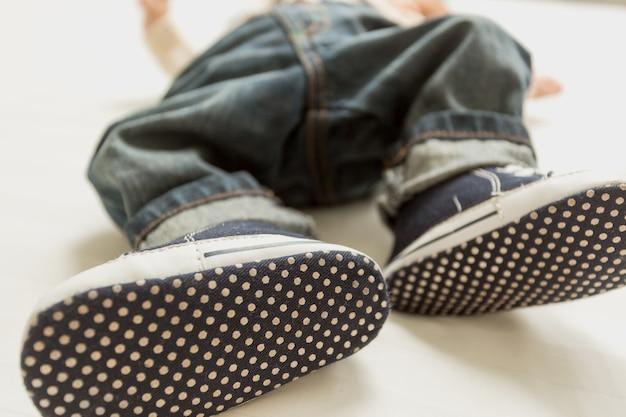 Zbliżenie zdjęcie stóp chłopca w dżinsach i trampkach
