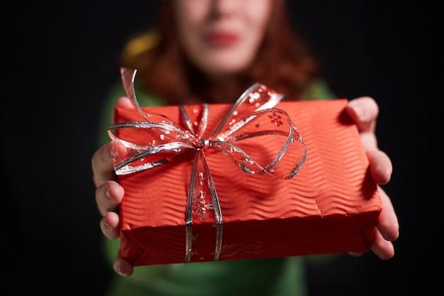 Zbliżenie zdjęcie szczęśliwej kobiety w świątecznym kapeluszu z prezentem w dłoniach na czarnym tle