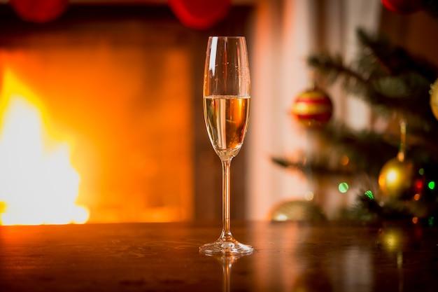 Zbliżenie zdjęcie szkła z szampanem na stole przed płonącym kominkiem