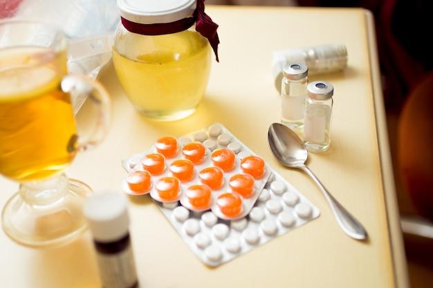 Zbliżenie zdjęcie tabletek w blistrze i słoik miodu na stoliku nocnym