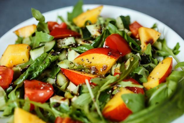 Zbliżenie zdjęcie zdrowej sałatki z rukoli, pomidorków cherry, szpinaku, awokado, nektaryny, nasion chia i posypane oliwą z oliwek i octem balsamicznym.